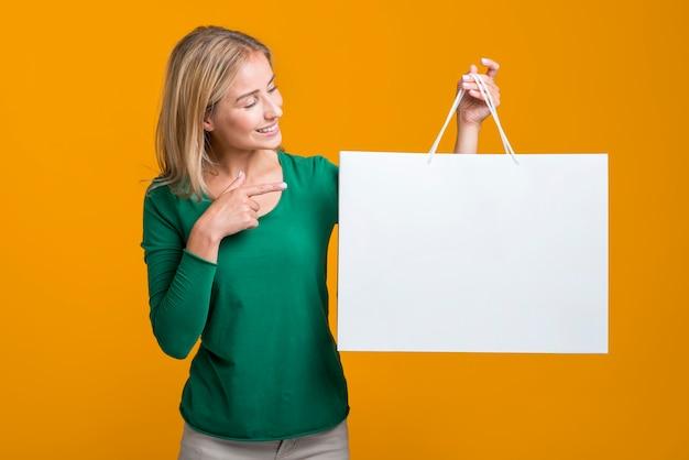 Mulher segurando e olhando para uma grande sacola de compras