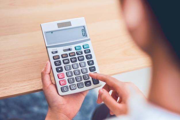 Mulher segurando e pressione a calculadora para calcular as despesas de renda e planos para gastar dinheiro no escritório em casa.