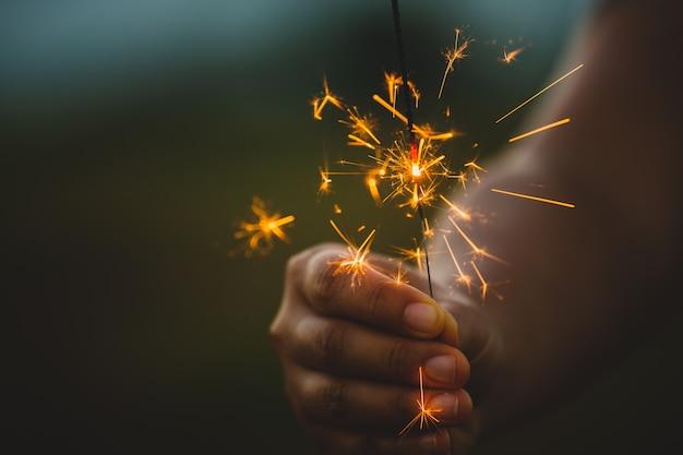 Mulher, segurando, e, tocando, com, fogo, sparklers, ligado, a, festival, em, a, arroz, campo, em, pôr do sol, tempo