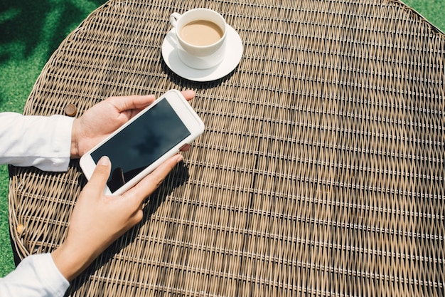 Mulher segurando e usando um telefone inteligente com tela preta em branco vazia no refeitório