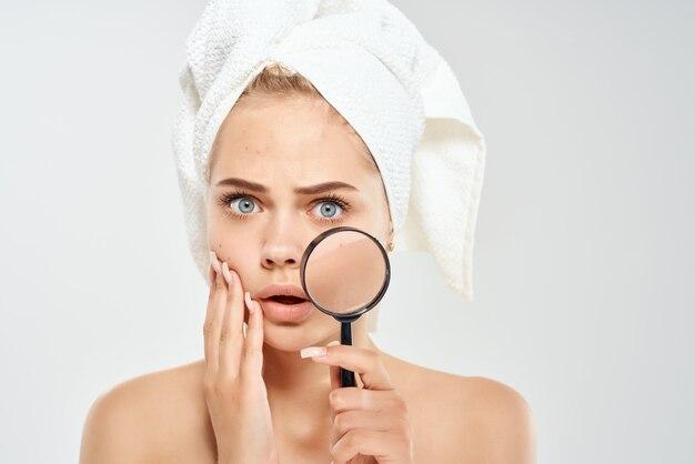 Mulher segurando e ver rosto lupa dermatologia closeup pele limpa