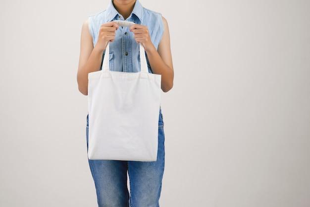 Mulher segurando eco saco de tecido isolar em fundo cinza