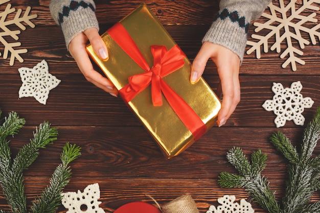 Mulher segurando embrulhado presente de natal nas mãos dela, ver os de cima