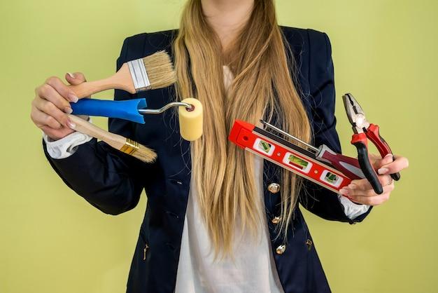 Mulher segurando escova, nível e outras ferramentas