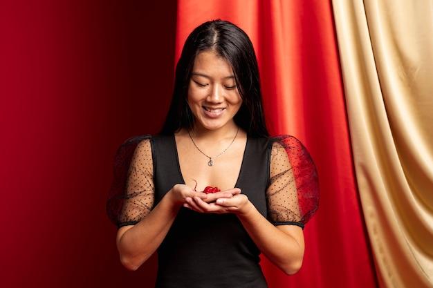 Mulher segurando estatueta de rato pelo ano novo chinês