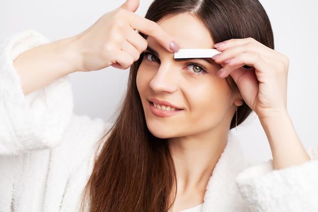 Mulher segurando faixa com cera para remover pêlos faciais