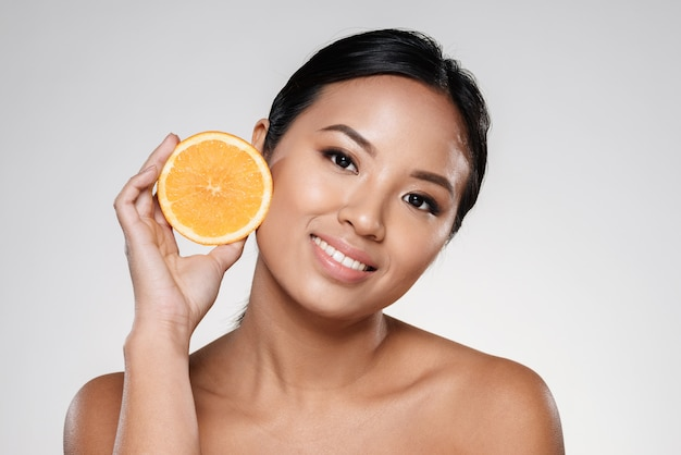 Mulher segurando fatias de laranja perto do rosto