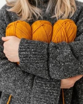 Mulher segurando fios de tricô laranja