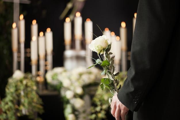 Mulher segurando flor branca no funeral