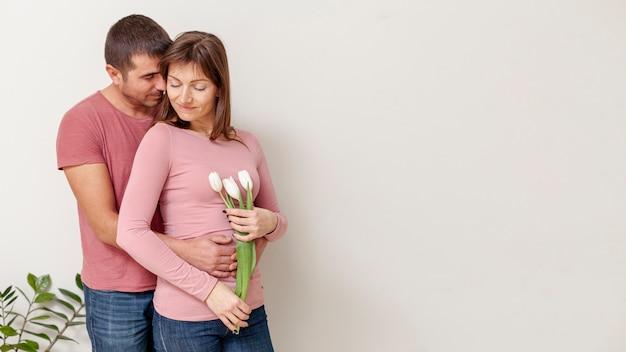 Mulher segurando flores e homem abraçando-a