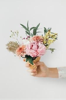 Mulher segurando flores em uma casquinha de sorvete