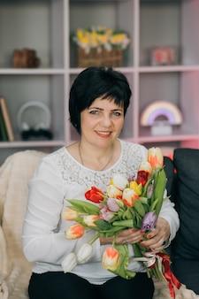 Mulher segurando flores na mão em casa