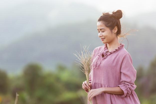 Mulher segurando flores no prado.