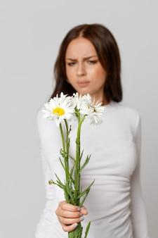 Mulher segurando flores, tendo uma reação alérgica à camomila