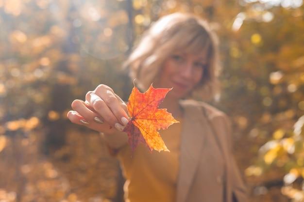 Mulher segurando folha de bordo amarela e laranja outono outono