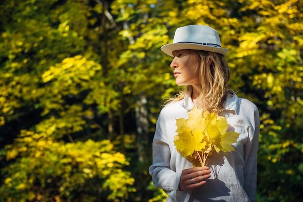 Mulher segurando folhas amarelas