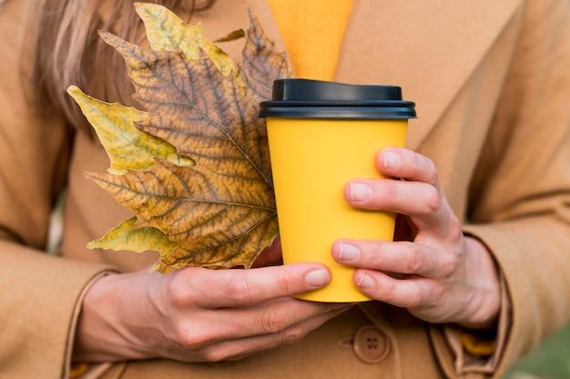 Mulher segurando folhas de outono e uma xícara de café