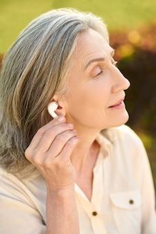 Mulher segurando fone de ouvido perto da orelha ao ar livre