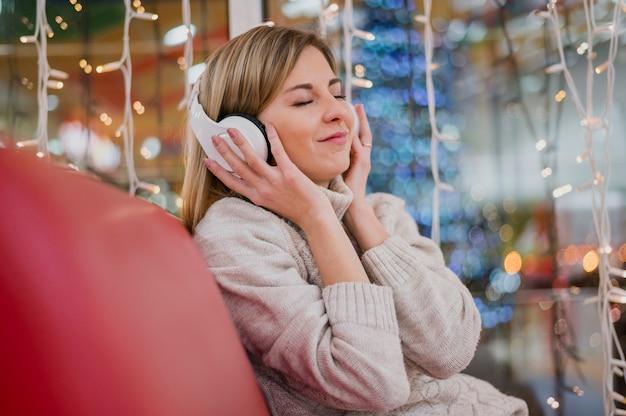 Mulher segurando fones de ouvido na cabeça e sentado no sofá perto de luzes de natal