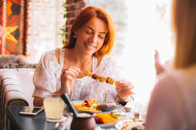 Mulher segurando frango grelhado no espeto