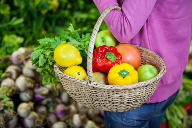 Mulher segurando frutas e legumes na cesta