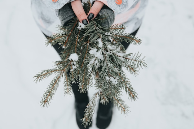 Mulher segurando galhos de pinheiro verde com neve no fundo desfocado