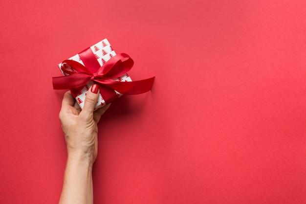 Mulher segurando giftbox de natal com laço vermelho