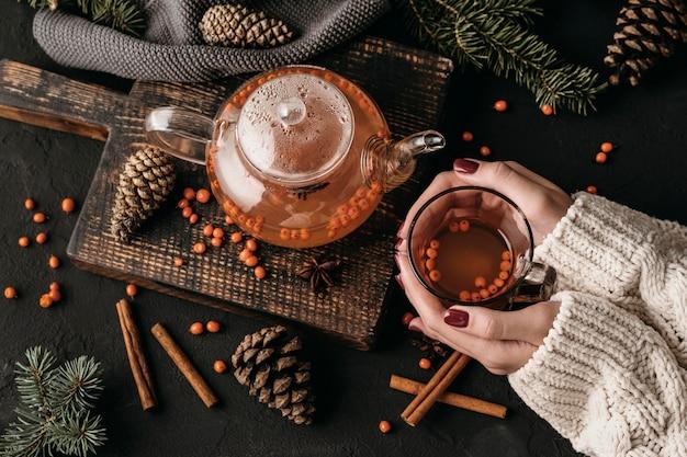 Mulher segurando glsss com chá de espinheiro