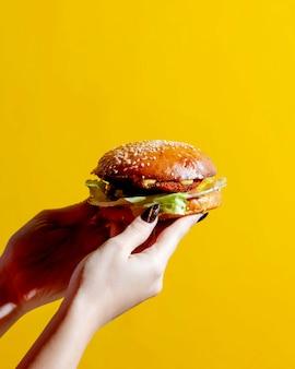 Mulher segurando hambúrguer nas mãos dela
