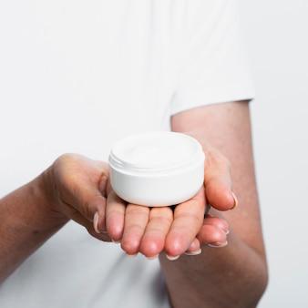 Mulher segurando hidratante nas mãos