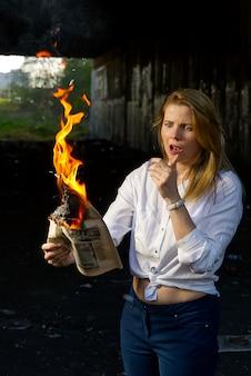 Mulher segurando jornal ardente.