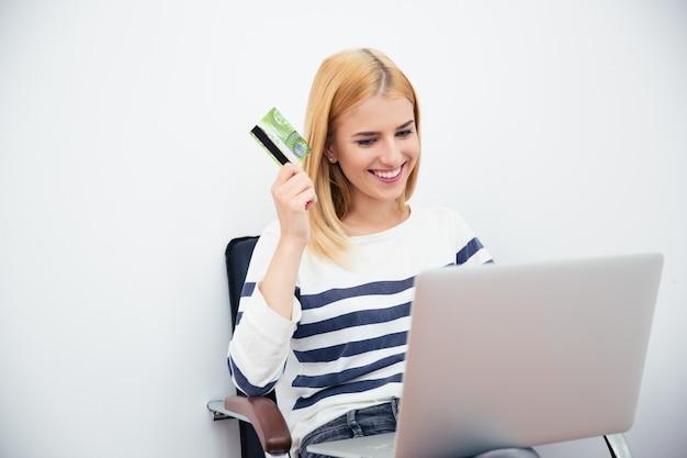 Mulher segurando laptop e cartão do banco