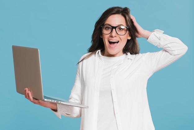 Mulher segurando laptop e estar espantado