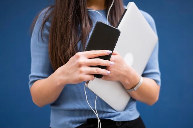 Mulher segurando laptop e smartphone com fones de ouvido