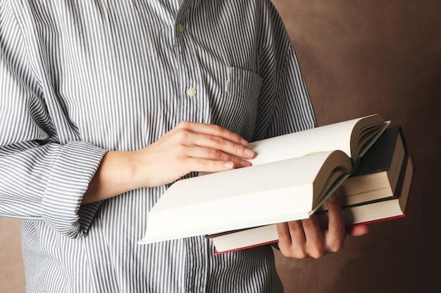 Mulher, segurando, livros, contra, fundo marrom, cima