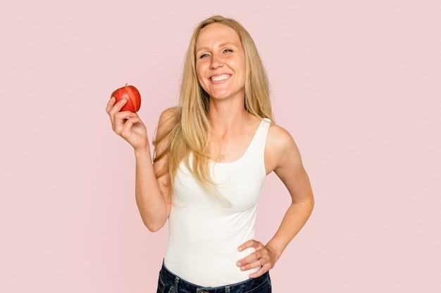 Mulher segurando maçã para campanha de alimentação saudável