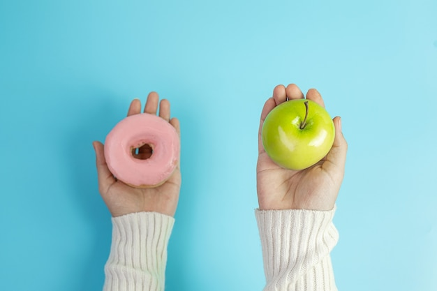Mulher segurando maçã verde e rosquinha rosa
