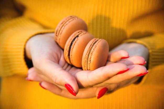 Mulher segurando macarons saborosos