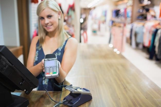 Mulher segurando máquina de cartão de crédito