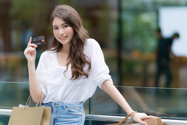 Mulher segurando muitas sacolas de compras com cartão de crédito e sorrindo na loja durante o processo de compra