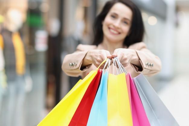 Mulher segurando muitas sacolas de papel multicoloridas em close da loja