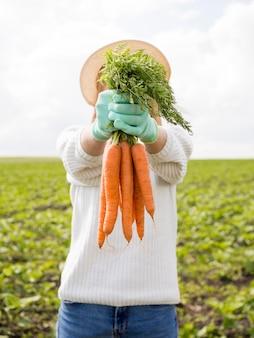 Mulher segurando na frente de suas cenouras