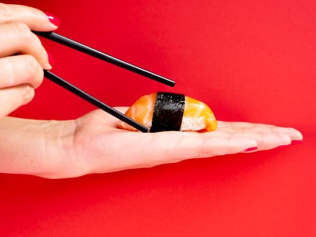 Mulher segurando na mão um sushi de salmão