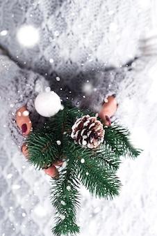 Mulher segurando nas mãos de madeira buquê decorativo de natal