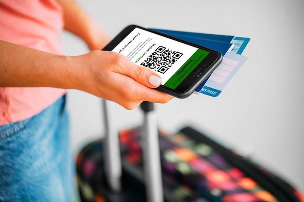 Mulher segurando no celular uma maquete do certificado de vacinação digital em uma das mãos e passaporte, máscara e tíquete na outra