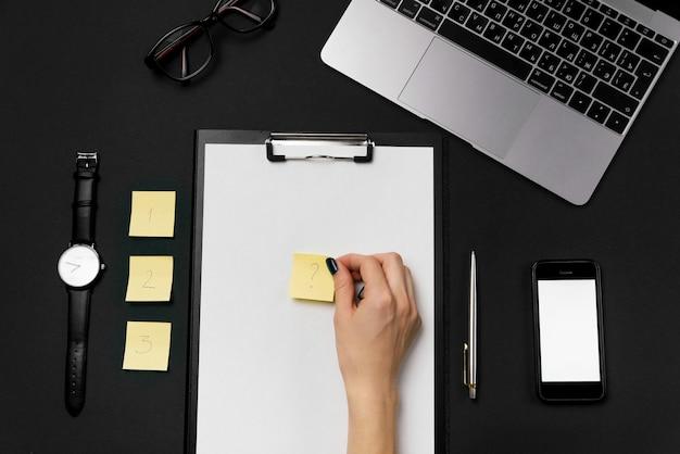 Mulher segurando no papel de mão amarelo para anotações com um ponto de interrogação. vista superior do desktop do escritório preto com laptop, telefone com tela branca e fundo de suprimentos.