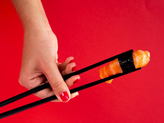Mulher segurando nos pauzinhos um sushi de salmão