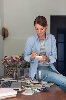 Mulher segurando notas posando na mesa