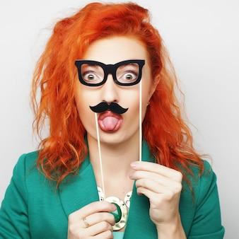 Mulher segurando o bigode e óculos no palito.