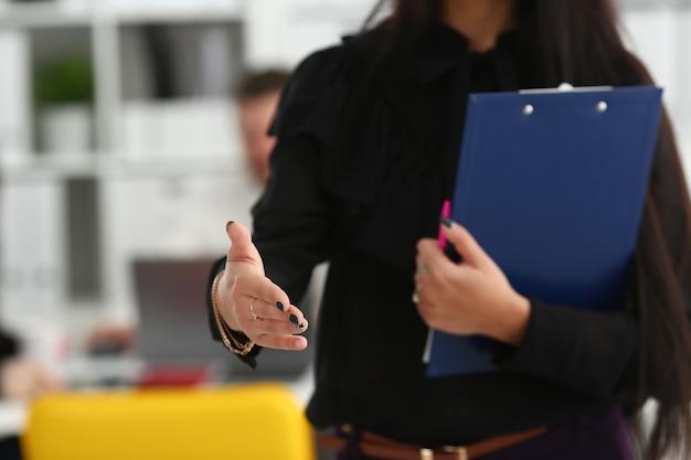 Mulher segurando o bloco de documentos e dando o braço para cumprimentá-lo